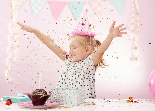 Cheerful child playing with colorful confetti in decorated room.
